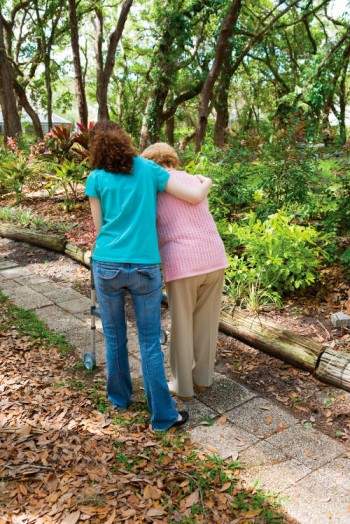 Caregiver helping senior woman walk through the park.  Vertical view with room for text.
